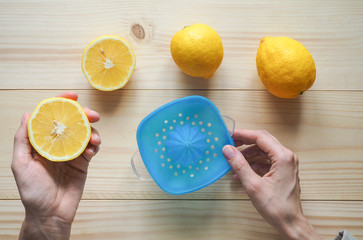 Hand squeezer with lemons on wooden background.