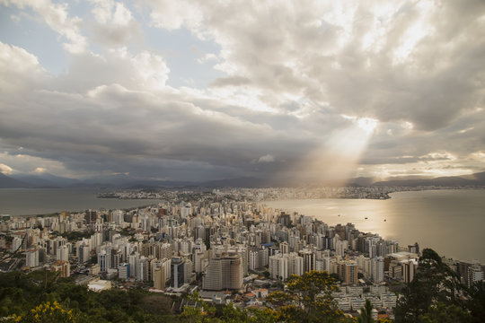 Panoramic view of the city's downtown. Light rays shining over the buildings and the bay. Rain clouds at distance, colorful clouds. Florianópolis, Santa Catarina / Brazil