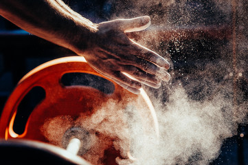 Male powerlifter hand in talc. preparation before lifting weights. Toned image.