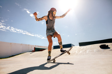 Female skater skateboarding at skate park.
