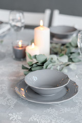 Wedding or festive table setting. Plates, wine glasses, candles and cutlery