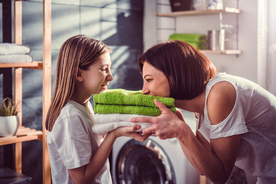 Mother and daughter smelling fresh towels