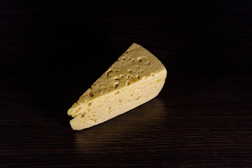 Piece of cheese on a wooden table