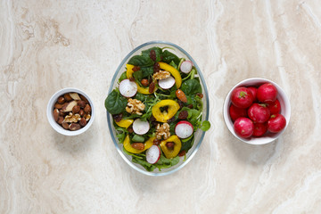 Healthy vegan salad with radish, nuts, yellow pepper on marble with copy space above and below