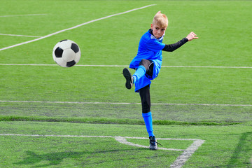 Teenage blonde Caucasian soccer (football) player in blue sport uniform is kicking ball in corner kick during game on grass field on sunny day