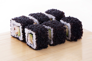 One set of California rolls covered black tobiko or masago caviar on a wooden board on a white background