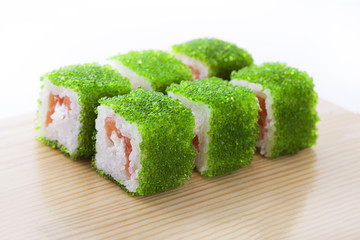 One set of California rolls covered green tobiko or masago caviar on a wooden board on a white background