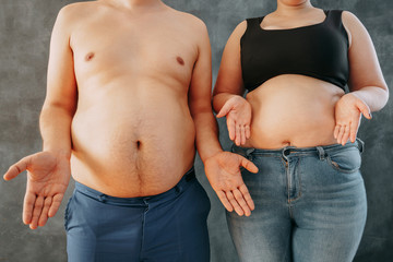 Overweight couple don't know how to lose, bewildered. Dieting, weight losing and health care concept