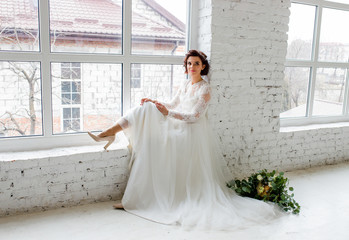 A beautiful brunette in a wedding dress with a bouquet in her hands sits on the windowsill