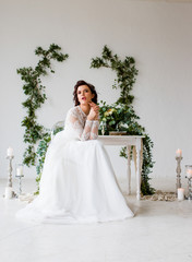 Portrait of an elegant bride. The wife is sitting in a white room decorated with green decor in a botanical style