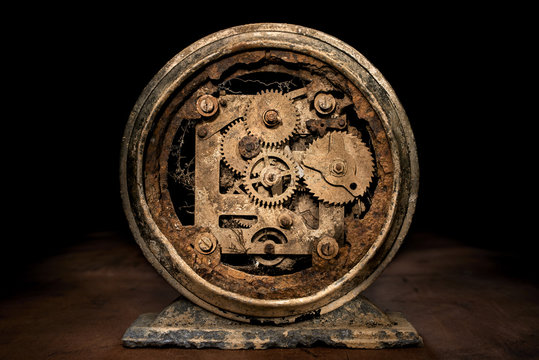 a rusted clock on a wood surface