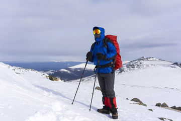 climber in mirror wind-proof glasses and a windproof mask with a backpack on a background of a winter mountain landscape