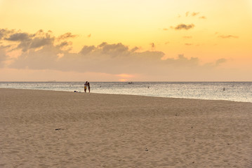 Caribbean beach at sunset with a couple