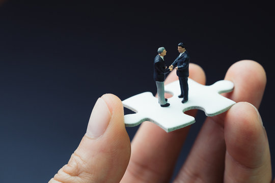 Business success strategy with collaboration, teamwork or negotiation jigsaw key, miniature people businessmen handshaking on white jigsaw puzzle piece in real human hand, dark black background