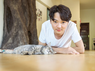 Handsome Chinese young man with cute tabby cat lying on the floor.