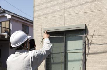 住宅とヘルメットの男性 現地調査 指差し タブレット