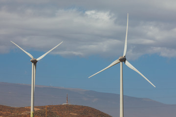electric wind turbines farm, blue sky background