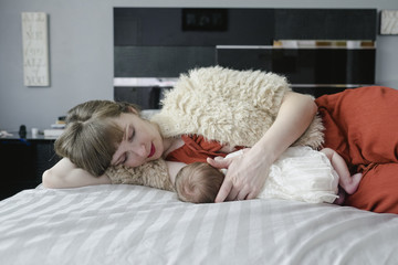 Mother breastfeeding newborn daughter while lying on bed at home