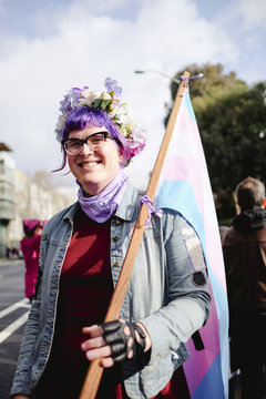 Portrait of woman holding flag while protesting on street against sky