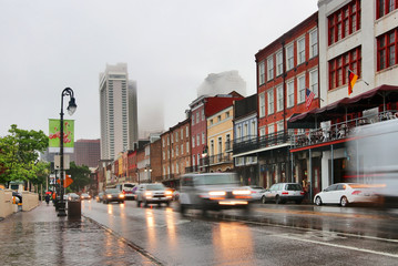 New Orleans cityscape during rainy day. Street view with French Quarter, Downtown buildings in a fog and cars in a motion on a wet road. Spring rain in New Orleans, Louisiana, USA.