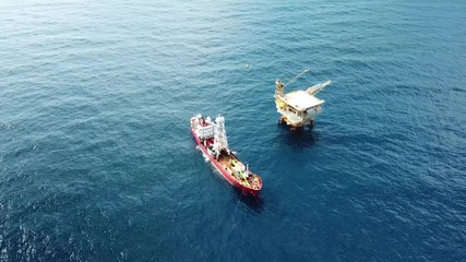 Wall Mural - An aerial view from a drone of a soil boring boat (a geotechnical drilling cum analogue survey vessel) close to a oil platform