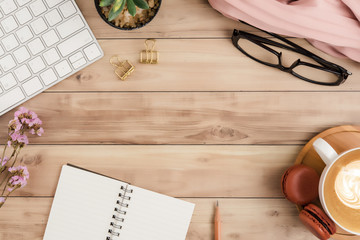 Flat lay top view office table desk. Workspace with blank note book, keyboard, macaroon, office supplies, flowers and coffee cup on wooden background.