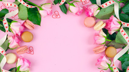 Happy Mother's Day background of pink roses and macaron cookies on pink wood table with copy space.