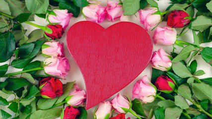 Red heart gift box surrounded by pink and red roses for Mother's Day, Valentine's Day or Birthday surprise overhead.