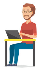 A bearded man wearing eyeglasses is operating a laptop computer