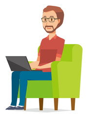 A bearded man wearing eyeglasses is sitting on a sofa and operating a laptop computer