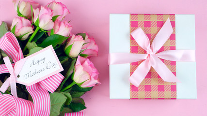Happy Mother's Day overhead with roses and gift on pink wood table.
