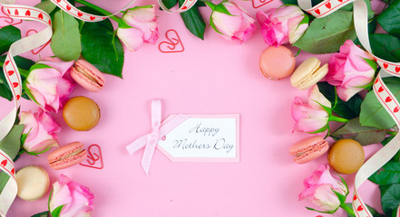 Happy Mother's Day background of pink roses and macaron cookies on pink wood table with gift card.