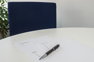 selective focus write business goals on mock up sheet with pen on office desk