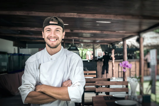 Portrait of a young smiling chef standing on the background of a summer restaurant