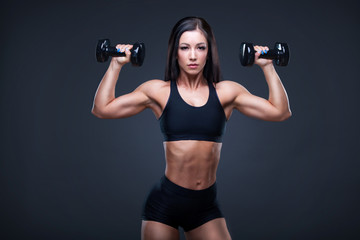 Brutal athletic sexy woman pumping up muscules with dumbbells. The concept of exercise sports, advertising a gym.