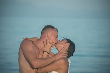 Passionate couple kissing on beach, sea water on background, copyspace. Honeymoon and vacation concept. Couple in love relaxing on holiday, honeymoon. Young lovers in sea.