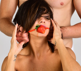 guy puts the strawberry gag in girl's mouth