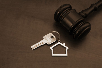 Gavel and key with kechain on wooden table
