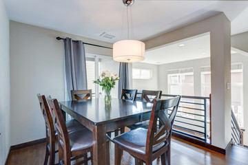 Light filled dining room with dark wood table set.
