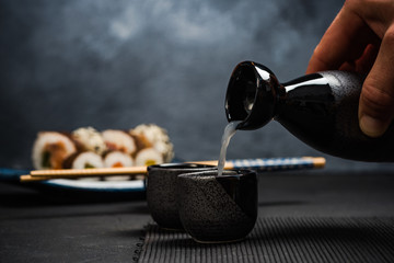 Man pouring sake into sipping bowl