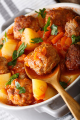 Meatballs tomato soup with vegetables and herbs close-up in a bowl. vertical