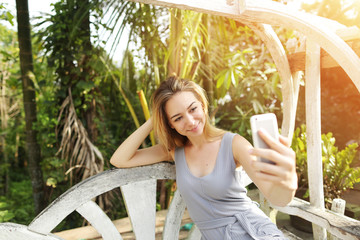 Young woman taking selfie with smartphone on sunny day, background of sunshine green palms in Thailand, Phuket. Concept of social networks, new technologies for better life, travel to tropical