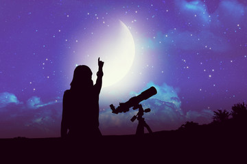 Silhouette of a girl beside astronomy telescope with Moon and Milky Way stars.