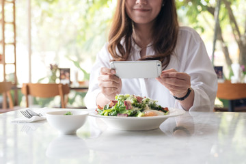 Closeup image of an asian woman using smartphone to taking photo of salad in a white plate on table in cafe