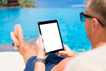 Man using tablet by the pool, blank white mock up screen