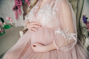 Pregnancy. The future mother in a luxurious negligee keeps her hands on her stomach.