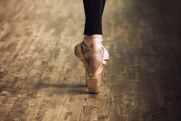 Feet of ballerina in training shoes on the parquet wooden floor close up retro style