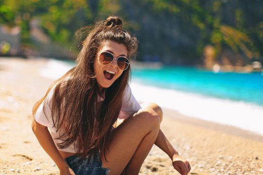 beautiful happy young woman wearing glasses and shorts resting on a turquoise beach, walking through the sand surrounded by beautiful nature, smiling and laughing, Fethiye, Oludeniz in Turkey
