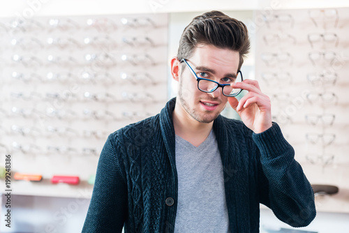 d0d6b7bc3c Man in front of shelf with glasses in optician shop looking at camera