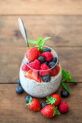 Chia. Superfoods breakfast with Chia seed pudding and  berries in a glass over wooden rustic background. Health concept, omega 3 product..